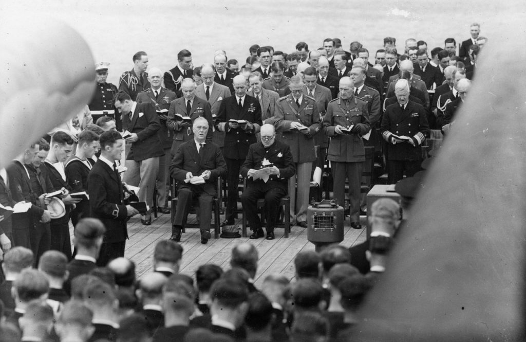 President Franklin D. Roosevelt and Prime Minister Winston Churchill at a church service framed by gun turrets aboard the HMS Prince of Wales on August 10, 1941